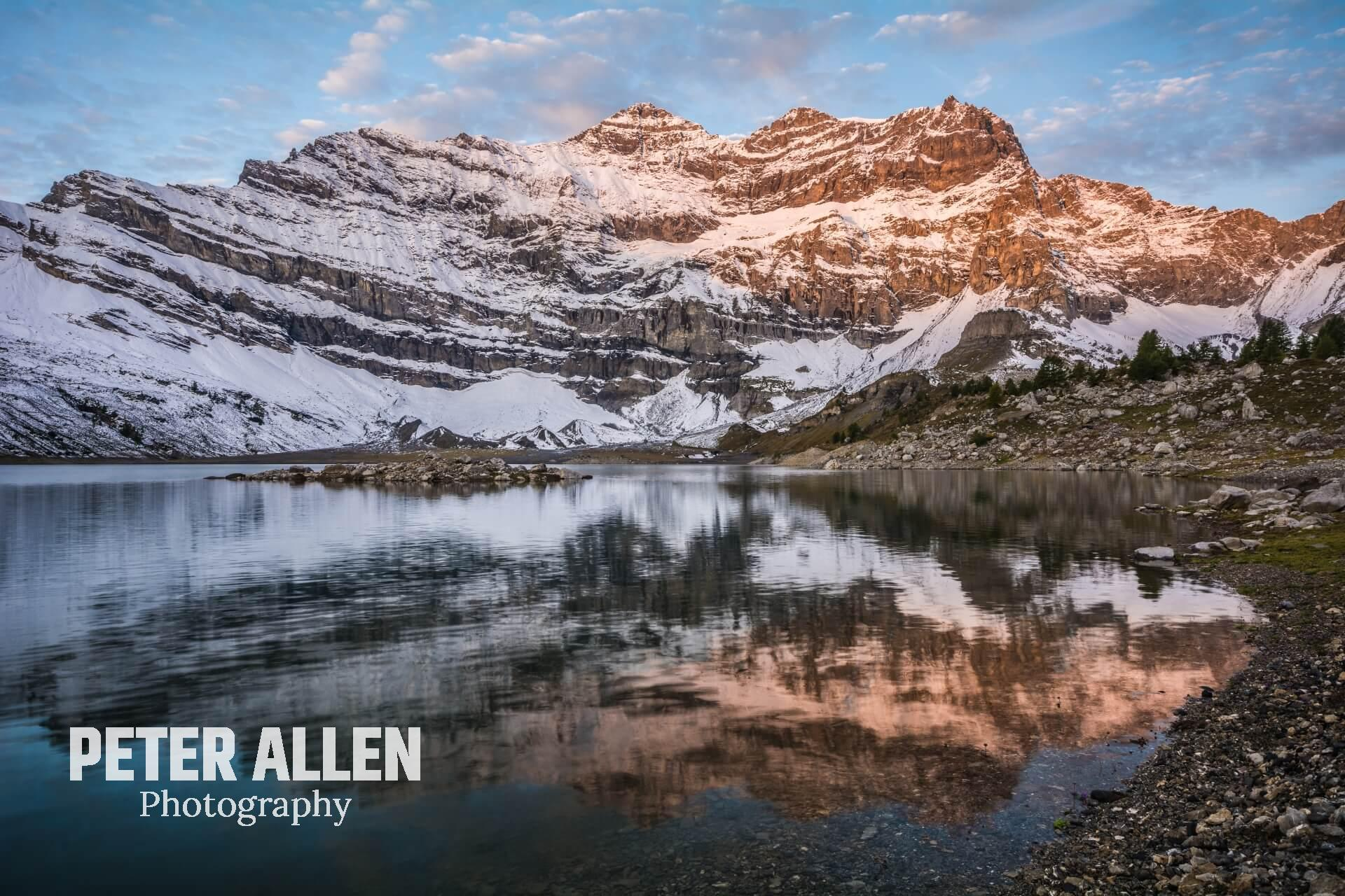 Lac de Salanfe with the first light of the day htting some of the mountains with a mirror-like reflection